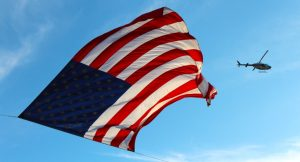 Image of an american flag with a helicopter. Vets 4212 report for affirmative action programs